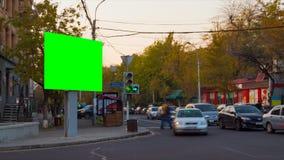 видео промежутка времени 4K Большое biilboard с зеленым экраном против предпосылок запачканных автомобилей и людей в городе осени сток-видео