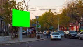 видео промежутка времени 4K Большое biilboard с зеленым экраном против предпосылок запачканных автомобилей и людей в городе осени видеоматериал