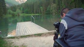 видео разрешения 4k человека принимая фото используя камеру dslr красивых озера и горы в задней части сток-видео