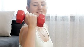 видео 4k красивой усмехаясь молодой женщины делая дома тренировки фитнеса с гантелями сток-видео