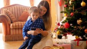 видео 4k усмехаясь молодой матери с ее шаржами мальчика наблюдая на мобильном телефоне под рождественской елкой акции видеоматериалы