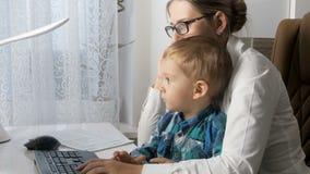 видео 4k элегантной молодой коммерсантки говоря телефоном и работая на компьютере пока сидящ с ее младенцем на офисе видеоматериал