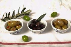 Вид 3 оливок и молодой оливковой ветки на салфетке ткани сверх Стоковое Изображение