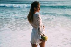 Вид от задней части нежной красивой девушки в белых прозодеждах мочит ноги в море, держит в ее руке большая свежую Стоковые Фото