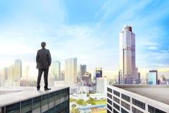 Вид сзади азиатского положения бизнесмена на крыше стоковое изображение rf