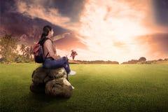 Вид сзади азиатской женщины путешественника сидя и наслаждаясь заход солнца VI Стоковые Изображения
