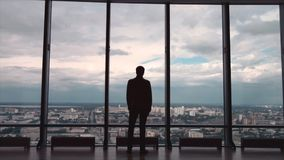 Вид сзади бизнесмена в офисе с панорамным видом на город Бизнесмен восхищает город от панорамного Windows стоковые фото