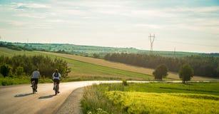 Вид сзади 2 велосипедистов ехать вниз с проселочной дороги через горы Случайные люди имея потеху задействуя вниз с пустой дороги стоковая фотография rf