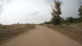 Вид сзади вождения автомобиля вдоль сельской грязной улицы сток-видео