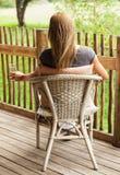 Вид сзади девушки сидя на веранде Стоковое Изображение