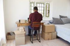 Вид сзади дела человека идущего от дома посылая товары стоковая фотография