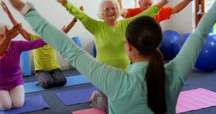 Вид сзади женского тренера тренируя старшие людей в тренировке на студии 4k фитнеса видеоматериал