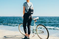Вид сзади женщины на обваловке на солнечном летнем дне стоковые изображения