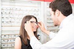 Вид сзади женщины порции офтальмолога для того чтобы выбрать стекла внутри стоковые изображения rf