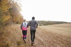 Вид сзади зрелых пар бежать вокруг поля осени Стоковая Фотография