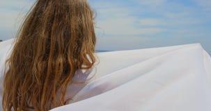 Вид сзади кавказской женщины в оболочке в саронге на пляже 4k акции видеоматериалы