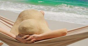 Вид сзади кавказской женщины ослабляя в гамаке на пляже 4k акции видеоматериалы