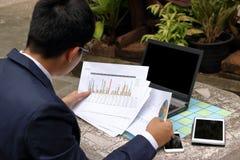Вид сзади красивого бизнесмена смотря диаграммы документов и думая о его работе в парке outdoors Стоковая Фотография