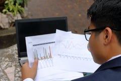 Вид сзади красивого бизнесмена смотря диаграммы документов и думая о его работе в парке outdoors Стоковое Фото