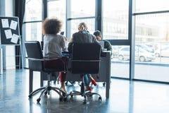 вид сзади многокультурных предпринимателей сидя на таблице стоковое фото rf