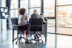 вид сзади многокультурных предпринимателей сидя на таблице стоковое изображение rf
