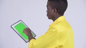 Вид сзади молодого счастливого африканского бизнесмена используя цифровой планшет акции видеоматериалы
