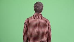 Вид сзади молодого человека хипстера ждать и думая акции видеоматериалы