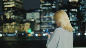 Вид сзади молодой женщины со смартфоном на предпосылке светов большой метрополии видеоматериал