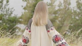 Вид сзади на милой кавказской женщине нося длинное положение платья моды лета на поле на предпосылке озера или акции видеоматериалы