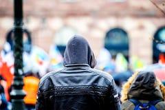 Вид сзади протеста пальто hoodie молодого человека наблюдения нося Стоковая Фотография RF