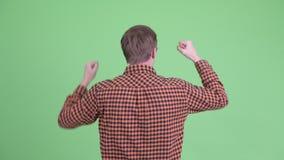 Вид сзади счастливого молодого человека хипстера с поднятыми кулаками сток-видео