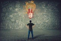 Вид сзади уверенного молодого человека, рук на бедрах, стоек перед стеной с вычерченной красочной электрической лампочкой и эскиз стоковые фотографии rf
