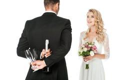 вид сзади холит удержание бутылки и стекел шампанского за задней невестой промежутка времени стоя перед им стоковые изображения rf