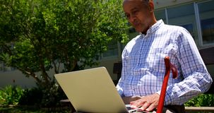 Вид спереди активного азиатского старшего человека используя ноутбук в саде дома престарелых 4k видеоматериал