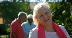 Вид спереди активной кавказской старшей женщины усмехаясь в саде дома престарелых 4k акции видеоматериалы