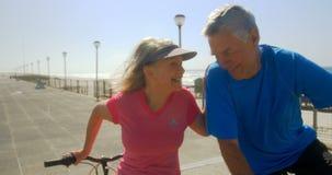 Вид спереди активных старших кавказских пар взаимодействуя друг с другом на прогулке на пляже 4k сток-видео