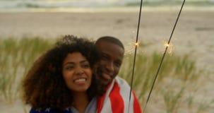 Вид спереди Афро-американских пар держа бенгальские огни в руках на пляже 4k видеоматериал