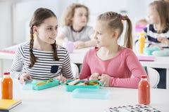 Вид спереди 2 девушек сидя столом школы с раскрытым lun стоковое изображение