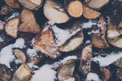 Вид спереди деревянных журналов штабелированных снаружи, предусматриванное в снеге Стоковое фото RF