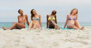 Вид спереди друзей смешанн-гонки женских ослабляя с глазами закрытыми на пляже 4k сток-видео