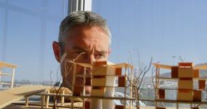 Вид спереди кавказских мужских архитекторов смотря строя модель в офисе 4k сток-видео