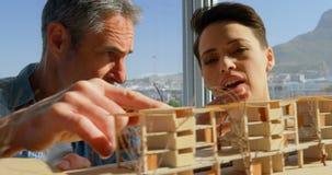 Вид спереди кавказского мужчины и женских архитекторов обсуждая над строя моделью в офисе 4k видеоматериал