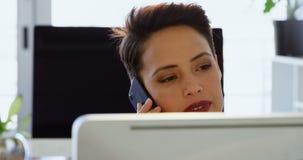 Вид спереди кавказской коммерсантки говоря на мобильном телефоне на столе в современном офисе 4k видеоматериал