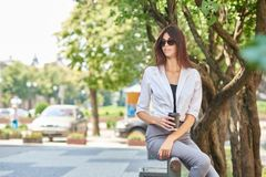 Вид спереди красивого молодого студента сидя на деревянной скамье стоковое фото rf