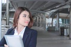 Вид спереди красивой молодой азиатской бизнес-леди держа связыватель кольца и смотря далеко на дорожке вне офиса с экземпляром Стоковые Изображения RF