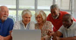 Вид спереди людей активной смешанн-гонки старших используя ноутбук на доме престарелых 4k видеоматериал