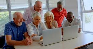 Вид спереди людей активной смешанн-гонки старших используя ноутбук на доме престарелых 4k сток-видео