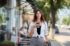 Вид спереди милого брюнет идя в кофе центра города выпивая стоковые фотографии rf