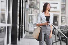Вид спереди милой модели представляя стоящий близко магазин, сумки нося и кофе стоковые изображения rf
