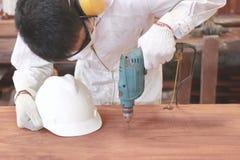 Вид спереди молодого азиатского работника с электрическим сверлильным аппаратом безопасности работая на деревянной доске в мастер стоковое изображение